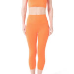 woman wearing orange color high waisted compression leggings, woman wearing high waisted compression leggings and top, high waisted Hurlingham legging
